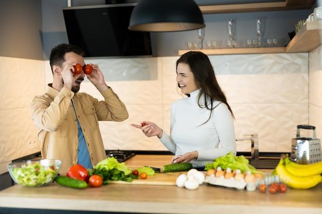 Милая пара улыбаются и веселятся на кухне. счастливые веганы готовят салат, используя только здоровую пищу.
