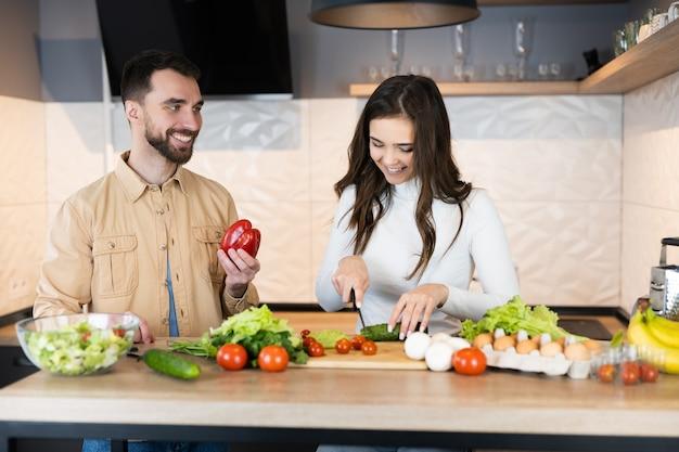 귀여운 커플은 요리하는 동안 시간을 보내고 부엌에서 함께하는 행복해 보입니다.