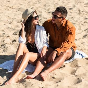 彼らの時間を楽しんでいるビーチでかわいいカップル