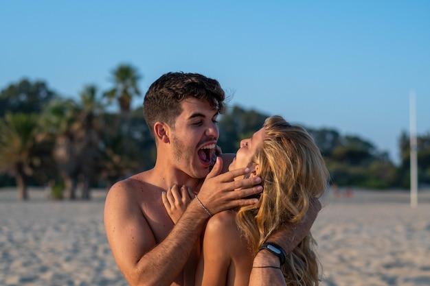 Милая пара на пляже обниматься и смеяться