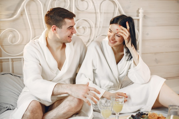 Cute couple in the bedroom wearing bathrobes having breakfast.