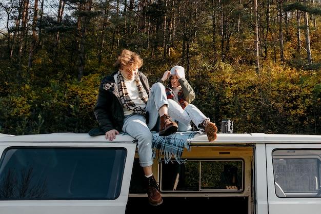 Милая пара, будучи рядом, сидя на фургоне снаружи