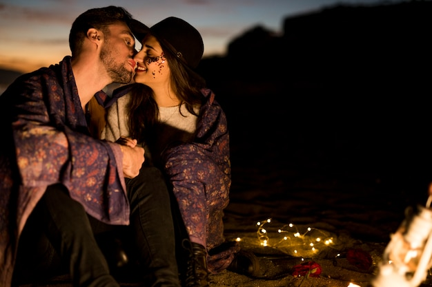 Cute couple in blanket kissing on sea shore