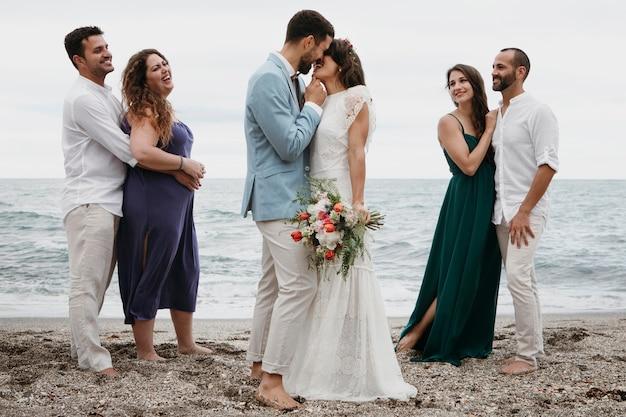 ビーチでの結婚式を祝うかわいいカップル