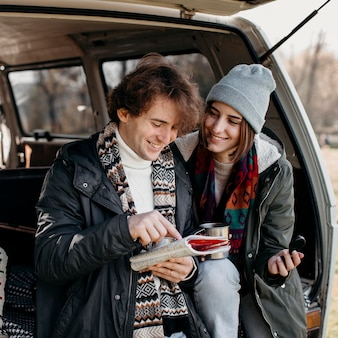 Cute couple checking a map while having a road trip