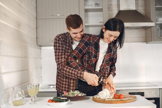 Coppie sveglie che cucinano nella cucina.