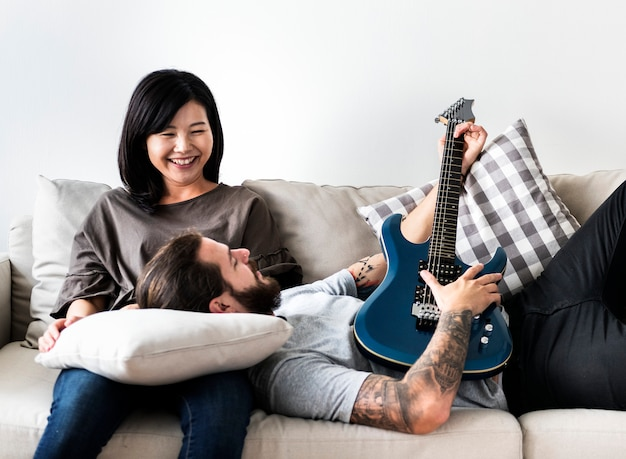 Cute couple on a couch boyfriend playing a guitar music and love concept
