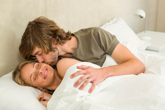Cute couple cuddling in their bed