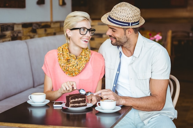 Cute couple on a date eating a piece of chocolate cake