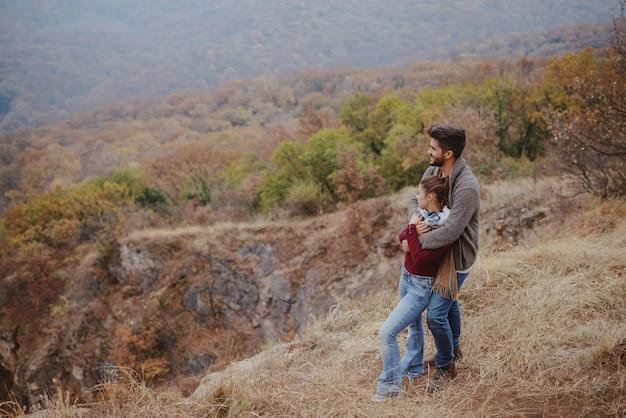 かわいいカップルは秋の視点でカジュアルな立って、抱き締めて美しい景色を見て服を着てください。