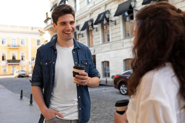屋外で一杯のコーヒーを楽しんでいるかわいいカップル