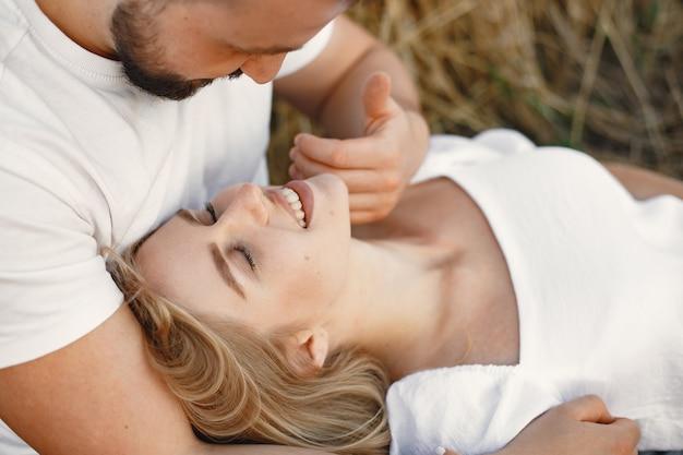 Coppia carina in un campo. signora in una camicetta bianca. ragazzo in camicia bianca