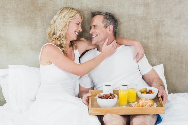 Cute couple having breakfast in bed in their room
