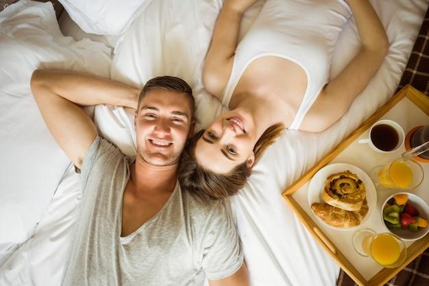ベッドで朝食をしているかわいいカップル