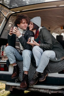 Cute couple holding cups of coffee in a van