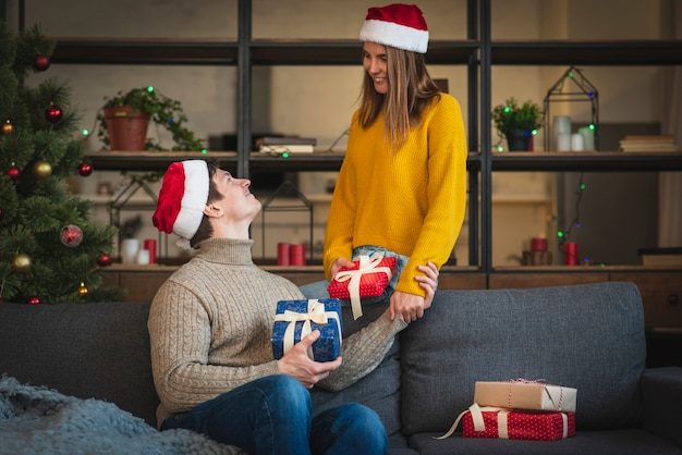 Cute couple holding gifts in living room