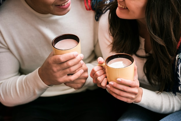 Cute couple holding hot drinks