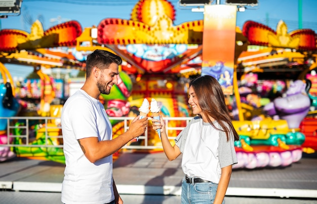 Cute couple holding ice creams at fair
