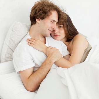 Cute couple hugging in bed medium shot