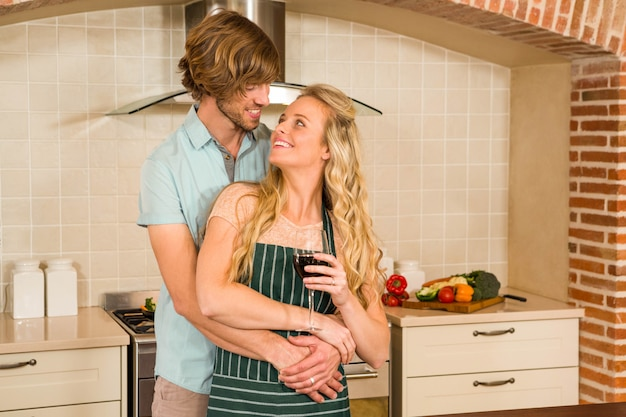Cute couple hugging and enjoying a glass of wine in the kitchen