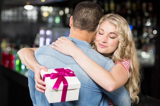 Милая пара обниматься с подарком