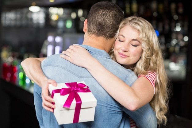 Cute couple hugging having a gift