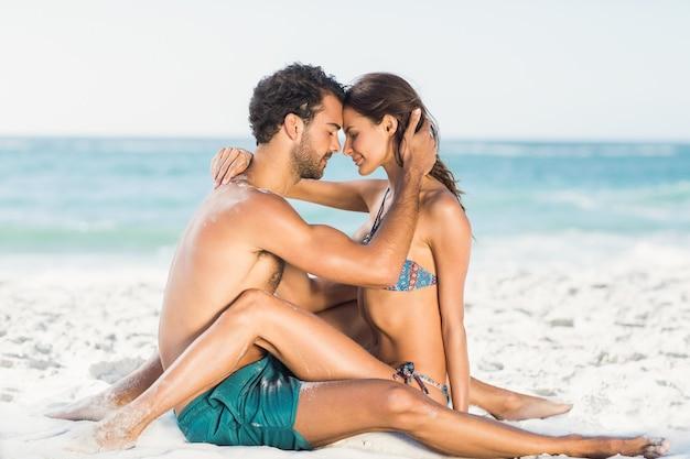 ビーチに座って抱き締めるかわいいカップル