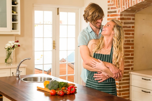Cute couple hugging with arms around in the kitchen