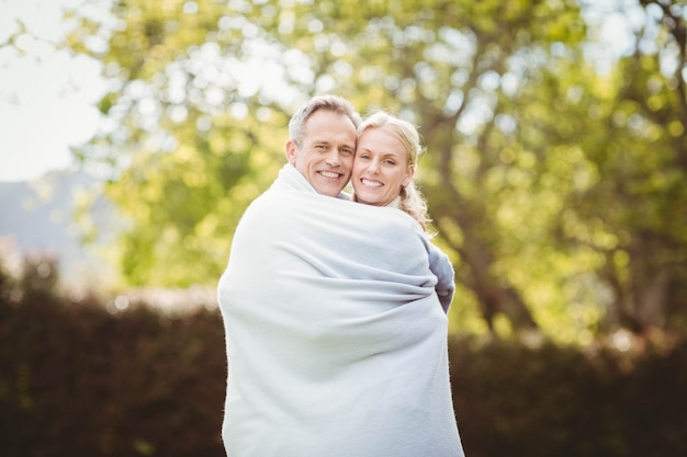 Cute couple hugging with a blanket around outside