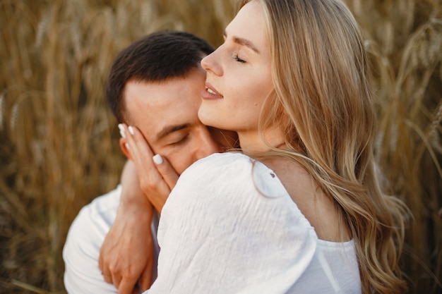 フィールドでかわいいカップル。白いブラウスの女性。白いシャツを着た男