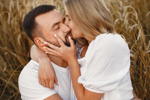 Милая пара в поле. дама в белой блузке. парень в белой рубашке
