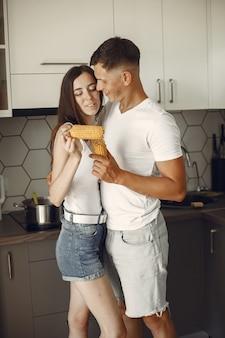 キッチンでかわいいカップル。白いtシャツを着た女性。家でペアになって、ゆでたトウモロコシを食べます。