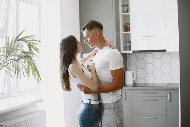 キッチンでかわいいカップル。白いtシャツを着た女性。自宅でペアリング