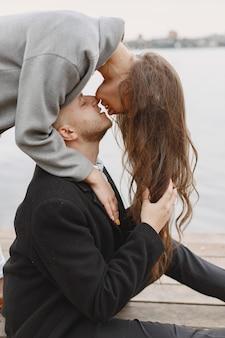 Милая пара в парке. дама в сером пальто. люди на пристани.