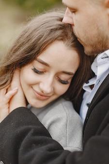 公園でかわいいカップル。灰色のコートを着た女性。桟橋の人々。