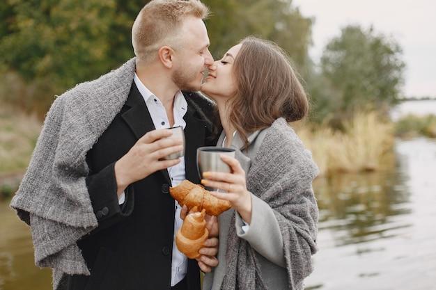 公園でかわいいカップル。灰色のコートを着た女性。魔法瓶とクロワッサンを持っている人。