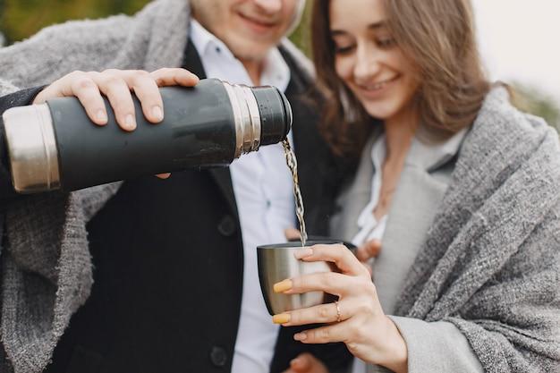 公園でかわいいカップル。灰色のコートを着た女性。魔法瓶を持っている人。