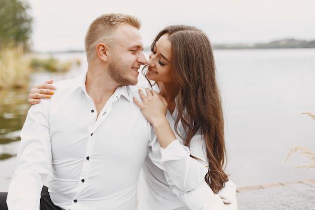 Милая пара в парке. дама в белой рубашке. люди на пристани.