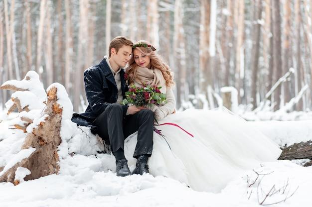 花束と恋にかわいいカップルが冬の森の背景にあるログに座っています。アートワーク。冬の結婚式。コピースペース