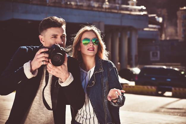 カメラで通りを歩くサングラスのかわいいカップル