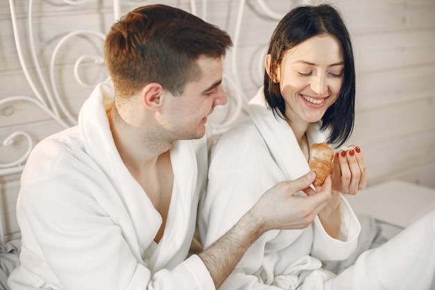 朝食を持っているバスローブを着ている寝室のかわいいカップル。