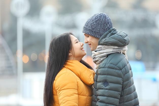 屋外で暖かい服を着たかわいいカップル