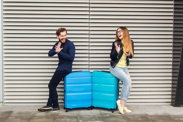 かわいいカップルは灰色の縞模様の背景に2つのスーツケースに寄りかかっています。彼女は長い髪、メガネ、黄色いセーター、ジャケット、ジーンズを持っています。彼は黒いシャツ、ズボン、ひげを着ています。彼らはお互いに満足しています。