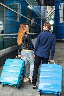 Cute couple is walking with suitcases outside in airport. she has long hair, glasses,  yellow sweater, jacket. he wears black shirt, beard. they are holding hands and smiling. view from back.