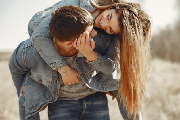 Cute couple in a jeans clothes in a spring field