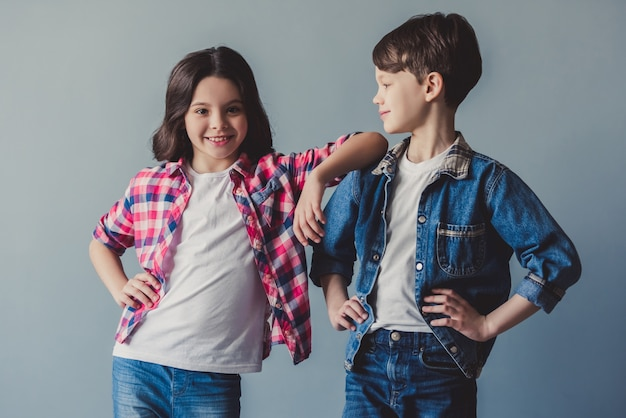 Cute couple of kids in casual clothes are posing and smiling