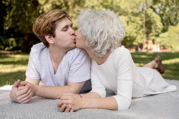 かわいいカップルが毛布で屋外キス