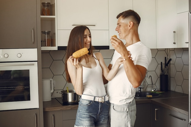 Cute couple in a kitchen. lady in a white t-shirt. pair at home eat boiled corn.