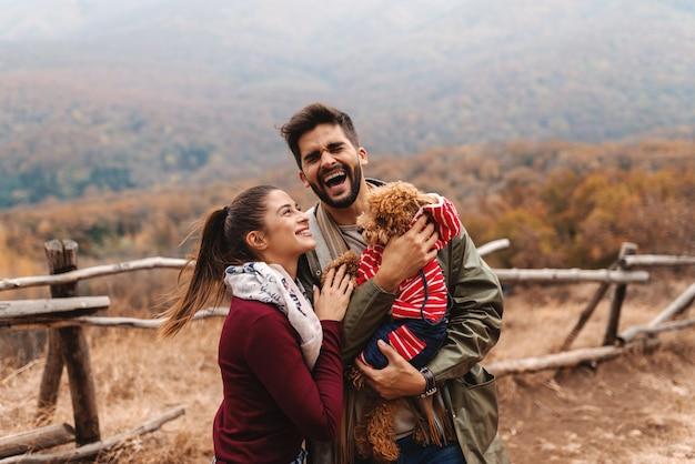 かわいいカップルが笑い、秋の時間に自然の中で立っている間アプリコットプードルで遊んで。