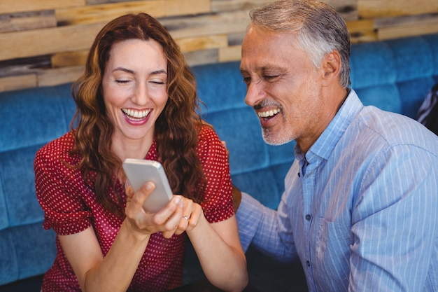 かわいいカップルは、携帯電話を見て